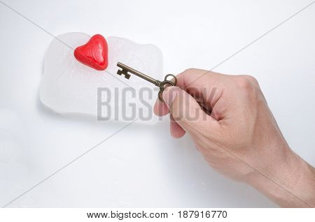 Man's hand holds a key from an icy heart