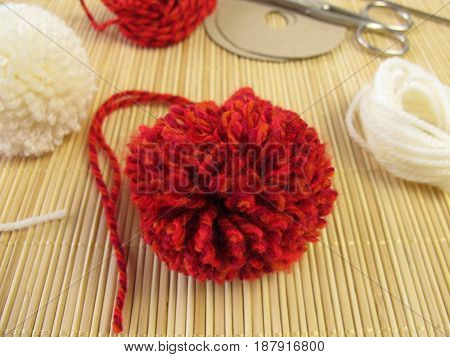 Making of small pompons in red and white