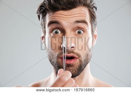 Shocked young man with tweezers looked camera isolated