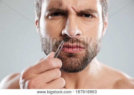 Young bearded man frowning and trying to tweezers hair in nose isolated