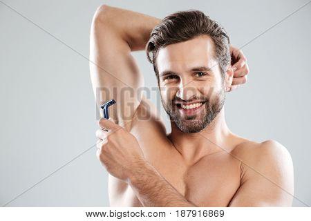 Smiling bearded man with razor smiling to camera while shaving armpits isolated