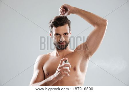 Young serious bearded man looking camera while using perfume isolated
