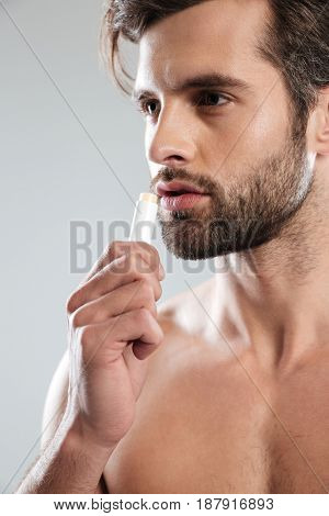 Young serious man using colorless lipstick isolated over grey