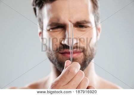 Close up shot of displeased bearded man holding tweezers isolated