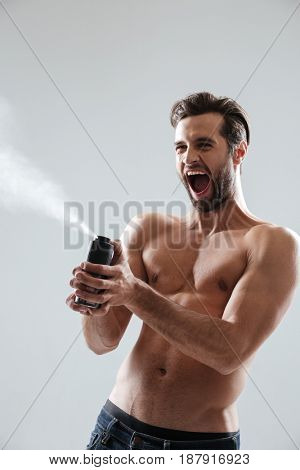 Angry bearded man playing with deodorant and screaming isolated