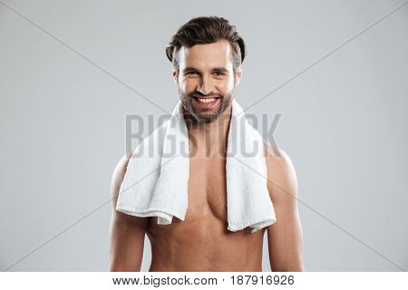 Young smiling man with towel on shoulders posing at camera isolated