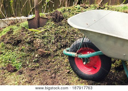 compost - garden plant fertilizer. wheelbarrow with spade poster