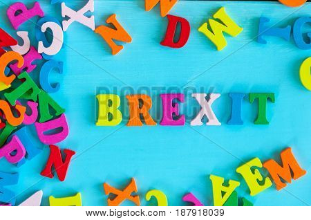 brexit or british exit - word composed of small colored letters on blue background.