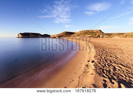La Higuerica beach in Aguilas, Murcia. A strecht of golden sand flanked by vegetation and dunes. A blue flag beach