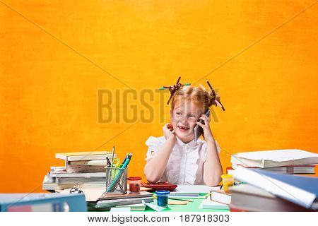 The Redhead teen girl with lot of books sitting with phone at table on orange studio background. The education and back to school concept