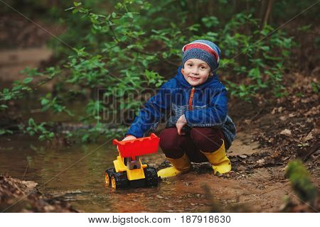 photo of little boy playing with toy truck