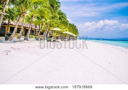 Tropical sandy beach at Panglao Bohol island with Sme Beach chairs under palm trees. Travel Vacation. Philippines.