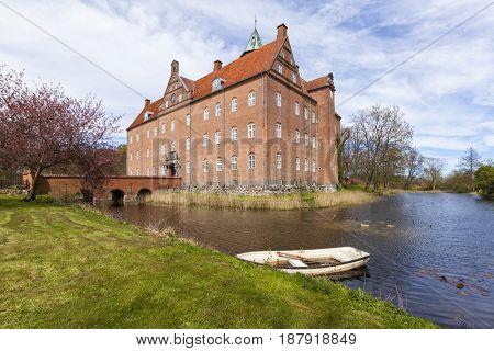 Water castle at Sostrup, Gjerrild, Jutland, Denmark, Boat on moat in foreground.