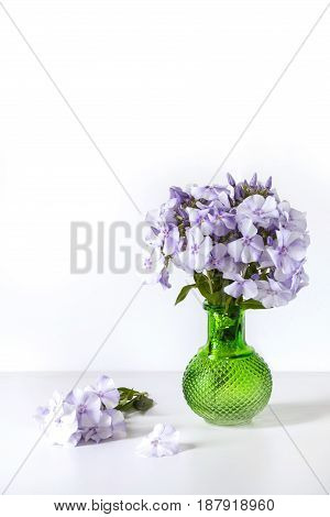 Bouquet of blue phlox in a green glass vase on isolated white background.