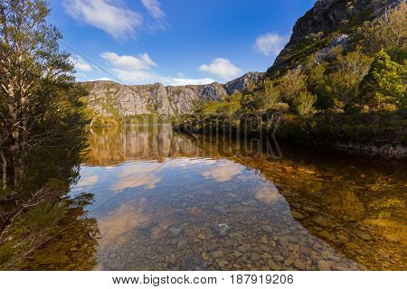 Clear water at the rocky bank of Crater Lake surrounded by mountains at Cradle mountain, Lake St Clair National Park. Autumn in Tasmania, Australia