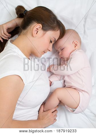 Mother and baby sleeping together, top view