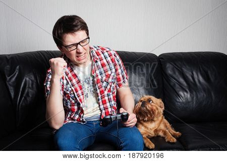 Young Man Playing Game At Home Playthrough Or Walkthrough Video. Attractive Man Is Wearing Eyeglasse