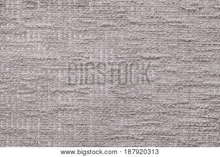 Light gray fluffy background of soft fleecy cloth. Texture of silver plush furry textile closeup.