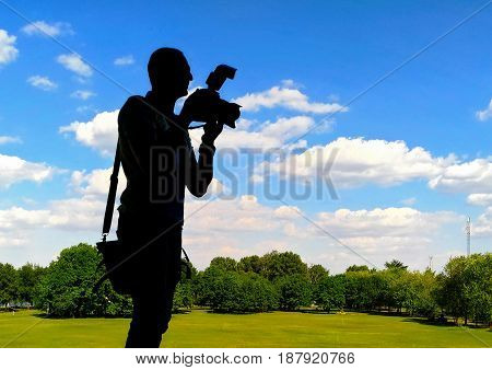Silhouette of photographer with camera against the background of green clipped lawn. He is standing by a small table