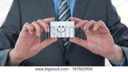 Digital composite of Midsection of businessman holding smiley face on card