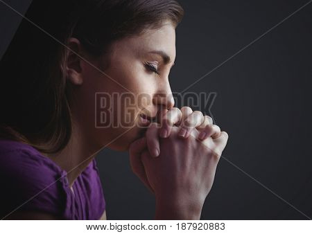 Digital composite of Woman praying against dark grey background