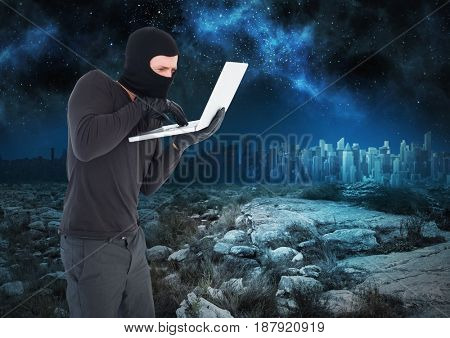 Digital composite of Criminal Man in balaclava on laptop in front of landscape at night