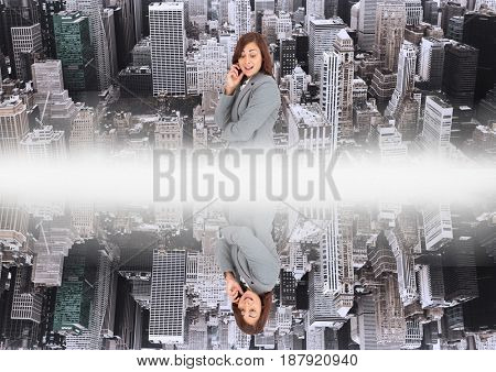 Digital composite of up side down city.mirror effect with white flares in the middle of two cities and woman looking down