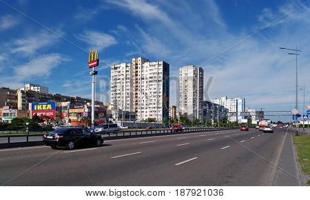 KIEV - UKRAINE - MAY 2017: A typical carriageway of the street in Kiev against the backdrop of a beautiful sky. Cars drive along the pavement, on which there are shops and apartment houses