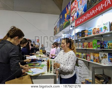 KIEV - UKRAINE - MAY 2017:  Art and book exhibition in Arsenal museum in Kiev. Visitors of the exhibition inspect the books. Book counter at the exhibition