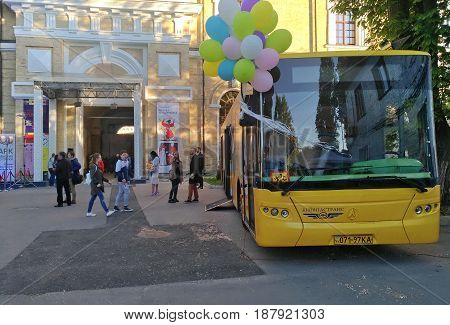 KIEV - UKRAINE - MAY 2017:  Art and book exhibition in Arsenal museum in Kiev. At the entrance to the exhibition is a yellow bus with colorful balloons