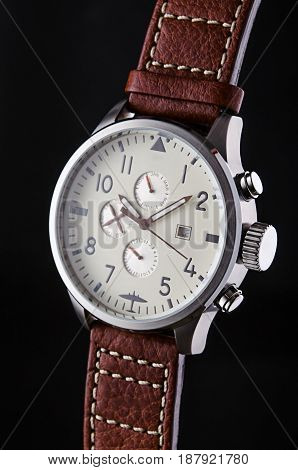Man's metal wristwatch with calendar and brown leather stitched wristlet on black background logos removed.