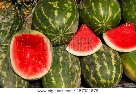 Water melons, some cut pieces to show the juicy insides