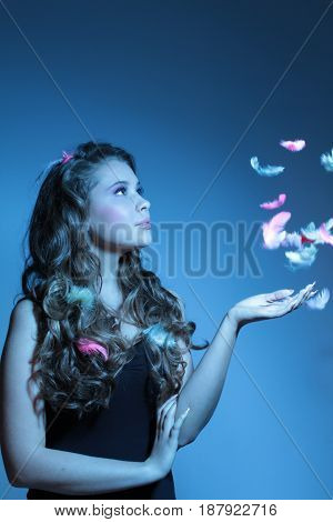 beautiful blue fashion shoot of young woman and feathers