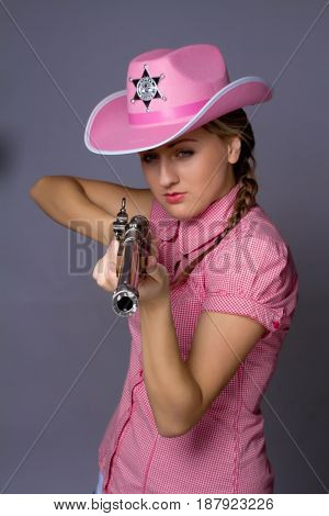 Shot of a beautiful glamour young girl with shotgun on gray