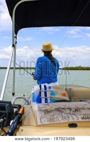 Naples, FL, USA - 03/16/2016: Adult female fishing off a boat in Marco Bay Florida