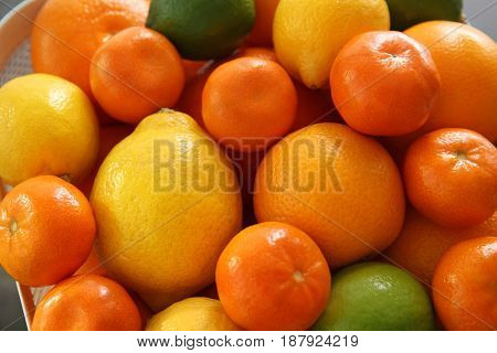 Fresh juicy citrus fruits in basket, closeup