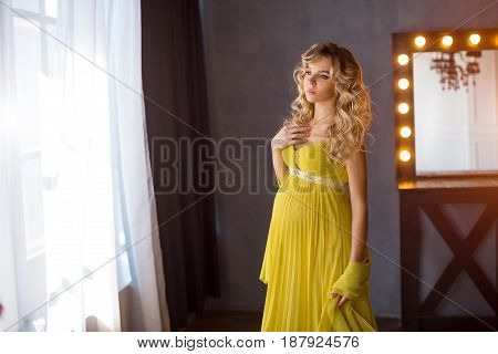 Pregnant woman. Romantic portait photo of beautiful blonde girl posing in sexy evening dress looking away near window. Indoor shot against gray wall and mirror.