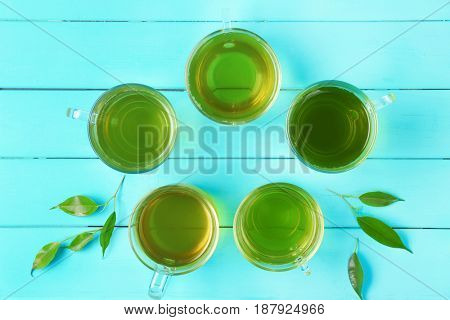 Cups of green tea on wooden background, top view
