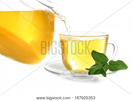 Pouring tea into glass cup from teapot on white background