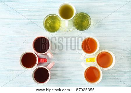 Cups of different tea on wooden table, top view