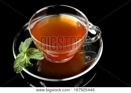 Cup of tea with mint leaves on dark background