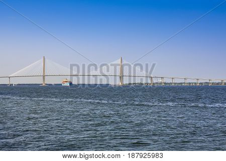 Charleston, SC, USA - 09/09/2016: Freighter ships passing under the Septima Clark Pkwy bridge on the Cooper River at Charleston SC