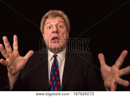 The surprised senior businessman against black studio background