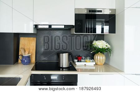 kitchen table top with stove, tray with coffee accesoires and flowers in vase
