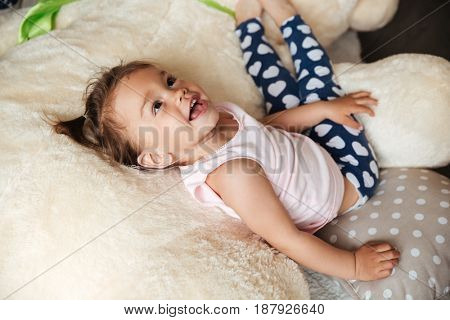 Image of little cute child girl lies on bed indoors. Looking aside.