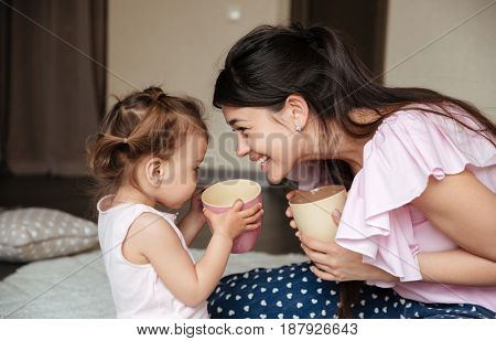 Image of happy young mother drinking tea with her little daughter sitting on bed indoors. Looking aside.