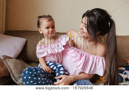 Picture of young mother sitting on sofa with her little daughter indoors. Looking aside.