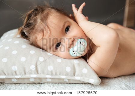 Photo of cute little girl child indoors with nipple lies on bed. Looking at camera.