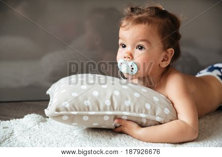 Image of pretty little girl child indoors with nipple lies on bed. Looking aside.