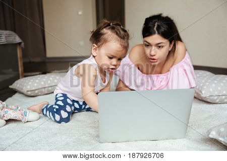 Picture of concentrated young mother with her little daughter lies on bed indoors using laptop computer. Looking aside.